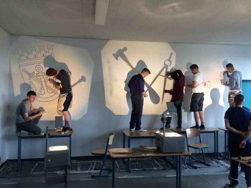 Die Motive der Wandgestaltung wurden mit Overheadprojektoren auf die Wand projiziert und mit verschiedenen Grautönen ausgelegt.